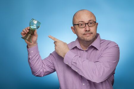 A businessman in a piked shirt pointing with the index finger on a antique glass of wine,  on the blue background.