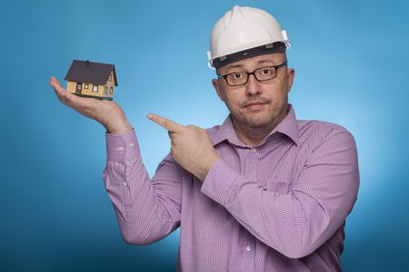 A businessman, architect in a piked shirt and hard hat  pointing with the index finger on a house,  on the blue background.
