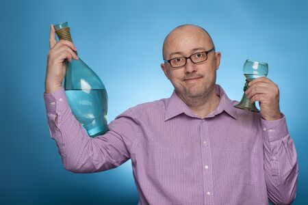 A businessman in a piked shirt has a bottle and a glass of wine in his hand,  on the blue background.