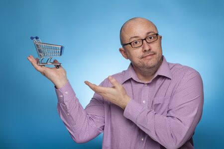 A businessman in a piked shirt pointing with the hand on a shopping cart,  on the blue background.
