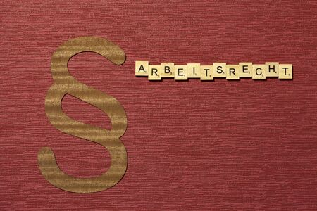 The sign paragraph on the claret color background. Its on the table. Word in german Arbeitsrecht