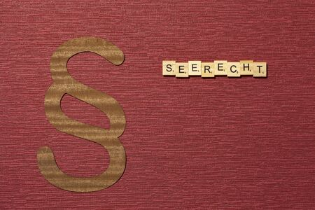 The sign paragraph on the claret color background. Its on the table. Word in german Seerecht