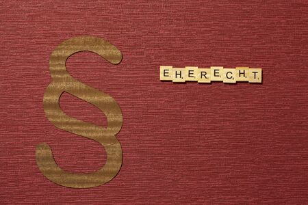 The sign paragraph on the claret color background. Its on the table. Word in german Eherecht