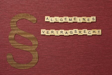 The sign paragraph on the claret color background. Its on the table. Word in german allgemeines Vertragsrecht