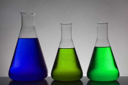Flüssigkeit in Laborflaschen. Wissenschaftliches biochemisches Labor. Bunte Flüssigkeit. Isoliert auf weißem Hintergrund, eine Gruppe von Flaschen. Reagenzgläser.