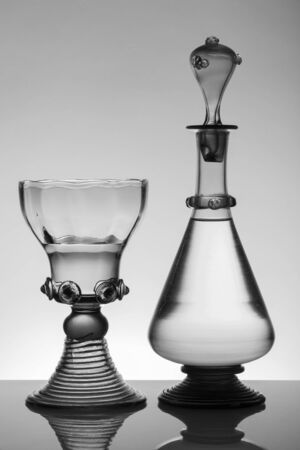 Middle age rummer wine glass and bottle on the white background. Black and white, monochrome picture.