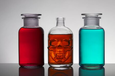 Liquid in laboratory bottles. Scientific biochemical laboratory. Colorful liquid. Isolated on white background, a group of bottles. Test tubes.