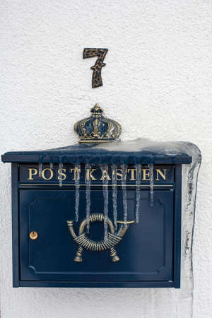 An iced mailbox hangs on the wall. Blue postbox overgrown with icicles.