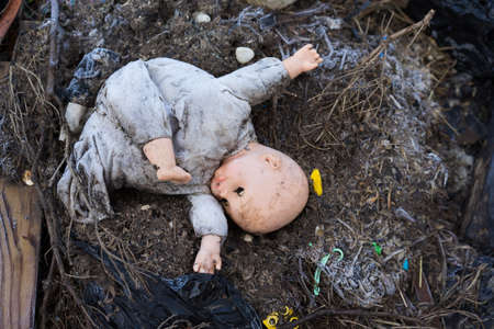 old dirty doll  on a burned ground, traces of the war and fire