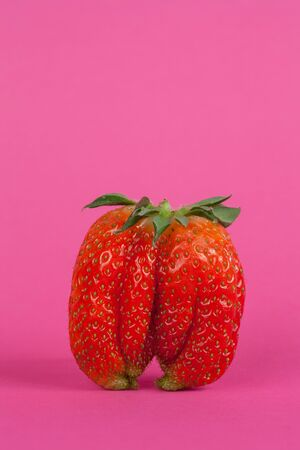 Strawberries isolated on a pink background, close up view