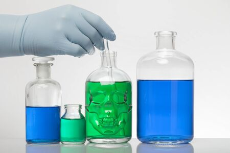 A hand in laboratory gloves mixes chemistry. Liquid in laboratory bottles. Scientific biochemical laboratory. Colorful liquid. Isolated on white background, a group test tubes.