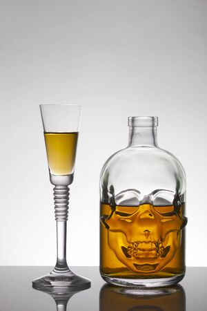 A skull bottle and crystal glasses with a liquid, alcohol drink.Colored watery drink absinthe, curacao, cognac.