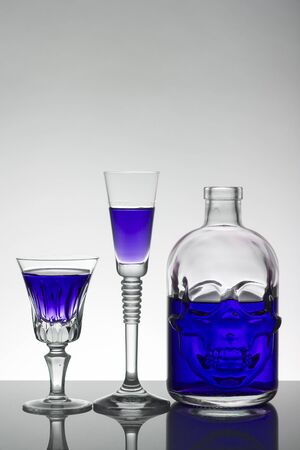 A skull bottle and crystal glasses with a liquid, alcohol drink.