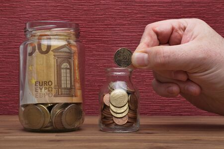 Hand holds euro coins and bill on the burgundy red background in a money box, isolated on the table