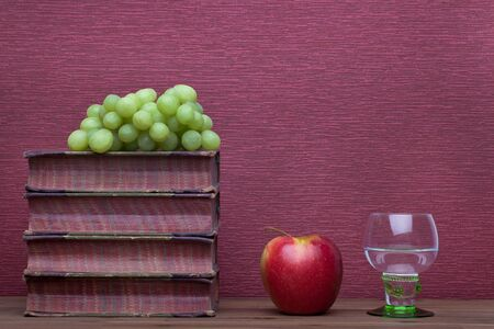 Renaissance, rummer wine glass, old books, apple and grapes on the burgundy background.