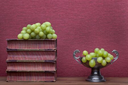 Renaissance, tin cup old books and grapes on the burgundy background.