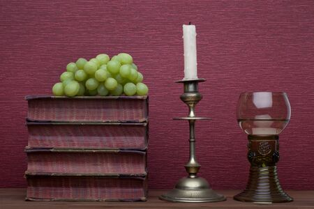 Renaissance, rummer wine glass, old books, grapes and candle holder on the burgundy background.