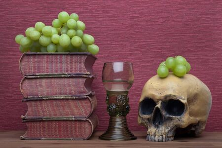 Renaissance, rummer wine glass, old books, human skull and grapes on the burgundy background. Stok Fotoğraf
