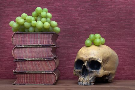 Old books, human skull and grapes on the burgundy background.