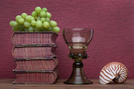 Renaissance, rummer wine glass, old books and grapes, nautilus on the burgundy background.