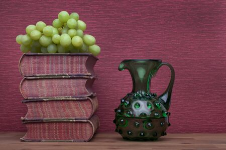 Renaissance, wine carafe, bottle, old books and grapes on the burgundy background.