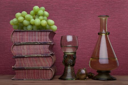 Renaissance, rummer wine glass, bottle, old books and grapes on the burgundy background.