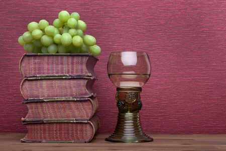 Renaissance, rummer wine glass, old books and grapes on the burgundy background. Stok Fotoğraf