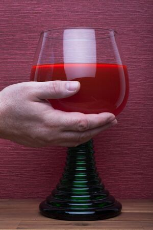 Hand holds rummer wine glass on the burgundy background.