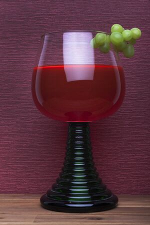 Rummer wine glass with green grapes on the burgundy background. Stok Fotoğraf