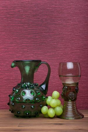 Renaissance, rummer wine glass and bottle with green grapes  on the burgundy background.