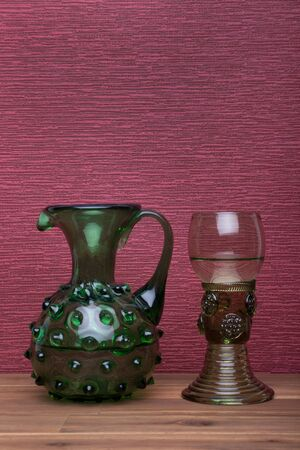Renaissance, rummer wine glass and bottle on the burgundy background.