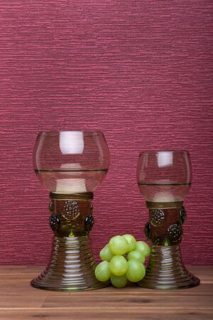 Two rummer wine glass with green grapes on the burgundy background. Stok Fotoğraf