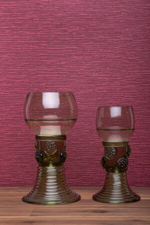 Two rummer wine glass  on the burgundy background.
