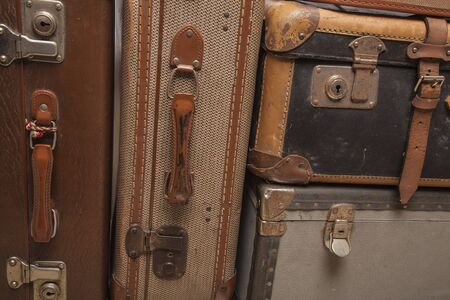 Old, retro, suitcases lie on the table with white background. Obsolete suitcase close up