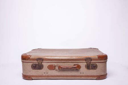 Old, retro, suitcases lie on the table with white background. Obsolete suitcase isolated on white background