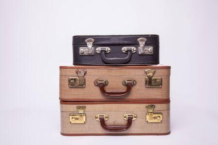 Vieilles valises rétro se trouvent sur la table avec un fond blanc. Valise obsolète isolé sur fond blanc