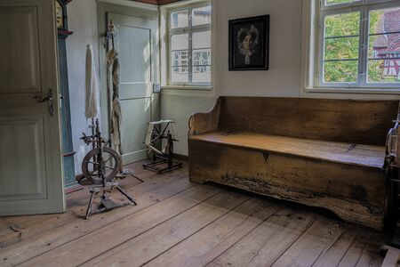 Schwaebisch Hall, Wackershofen, Germany - 15 October 2019: Interior views of a german village house. View of an old German spinning wheel and wooden bench