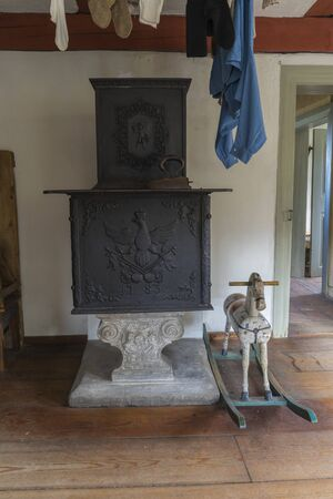 Schwaebisch Hall, Wackershofen, Germany - 15 October 2019: Interior views of a german village house. View of a wood stove in the living room