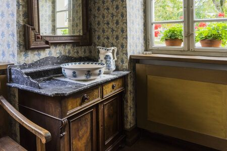 Schwaebisch Hall, Wackershofen, Germany - 15 October 2019: Interior views of a german village house. View in a german peasant bedroom with wash bowl on dresser