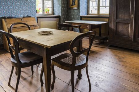 Schwaebisch Hall, Wackershofen, Germany - 15 October 2019: Interior views of a german village house. View from an old rustic wooden dining table with the cupboard Editöryel