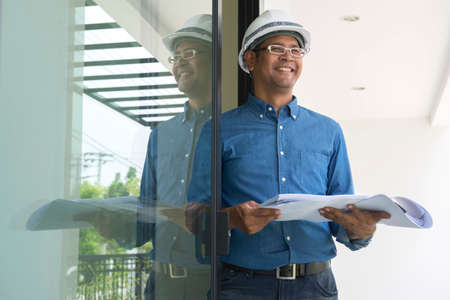 construction safety: architect with hard hat at construction site