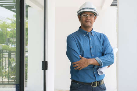 indian business man: architect with hard hat at construction site