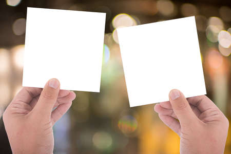 show of hands: hand hold blank square paper over blur background
