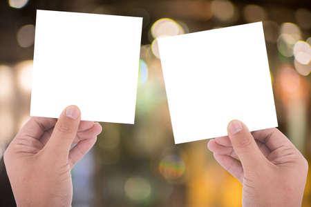 alzando la mano: hand hold blank square paper over blur background