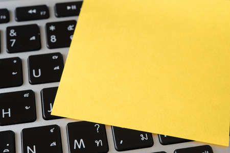 recollection: blank yellow note paper with computer in background