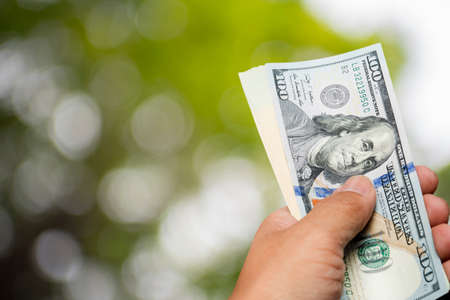 one hundred dollar bill: hand hold one hundred dollar bill over blur tree background