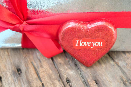heart shaped stuff: heart shape paper with word I love you on wood floor Stock Photo