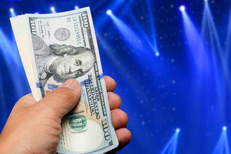 one hundred dollar bill: hand hold one hundred dollar bill over beautiful lights