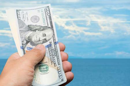 one hundred dollar bill: hand hold one hundred dollar bill over blue sky