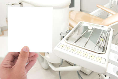 scaler: hand hold blank card and dental clinic equipment on metal plate in background